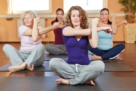 crosslegged: Four happy women exercising cross-legged together in a fitness center Stock Photo