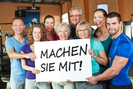Happy group holding German sign in fitness center saying Join us Foto de archivo