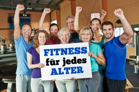 health club: Cheering group in health club holding German sign saying Fitness for every age Stock Photo