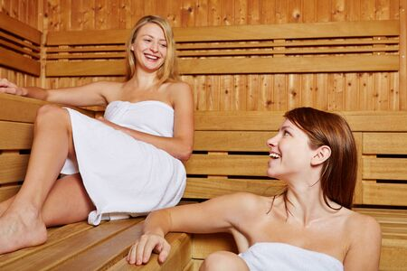 Two female friends chatting in a sauna photo