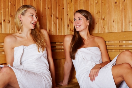 Two happy women talking to each other in a sauna photo