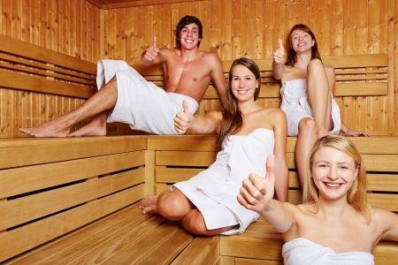 Quatre personnes heureuses dans un sauna tenant leurs pouces vers le haut