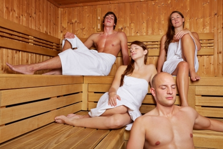 Relaxed people sitting together in a sauna with their eyes closed photo