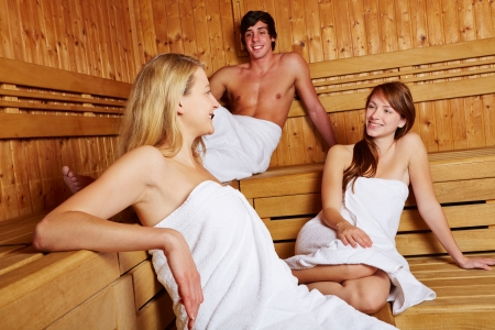 woman in towel: Man and women in mixed sauna talking and smiling Stock Photo