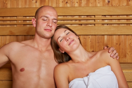 Young couple relaxing in a wooden sauna with their eyes closed photo