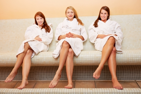 The attractive smiling women sitting on a heat bench photo