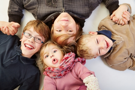 numerous: Four happy siblings in a circle looking up