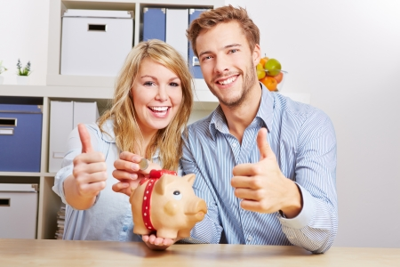 piggy bank money: Smiling happy couple with piggy bank and monay holding their thumbs up