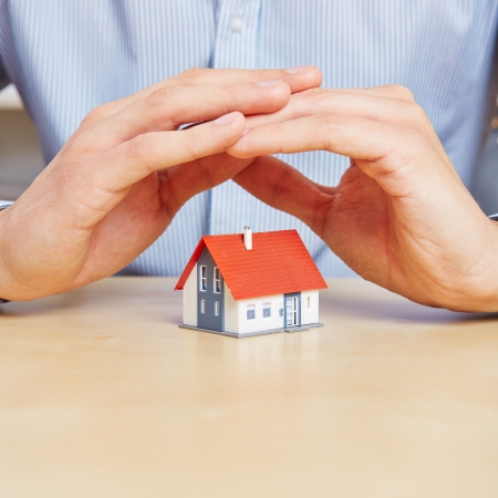 household insurance: Man holding his hands over a small house to protect it Stock Photo