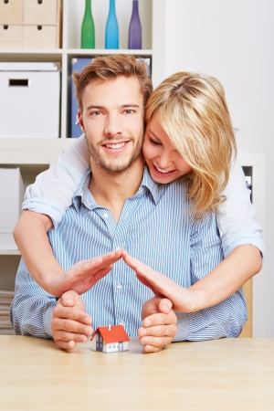 household insurance: Happy couple holding their hands protectivly over a small house