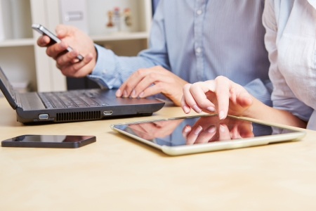 tabla de surf: Los hombres de negocios que trabajan en el escritorio con una computadora tablet y smartphones Foto de archivo