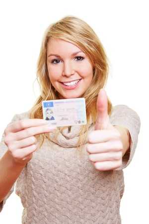 aandrijvingen: Jonge gelukkige vrouw met haar nieuwe Europese rijbewijs die de duimen omhoog Stockfoto