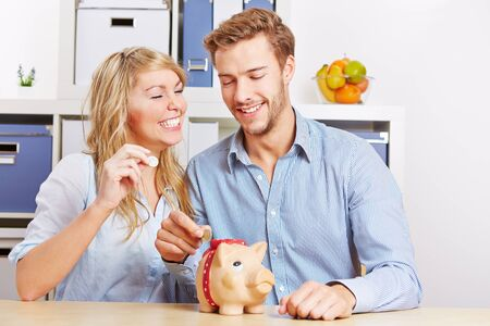Happy couple putting Euro mony coins in a piggy bank photo