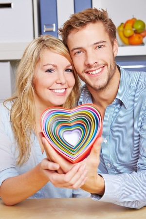 Smiling happy couple holding many colorful hearts in a living room Stock Photo - 16971722