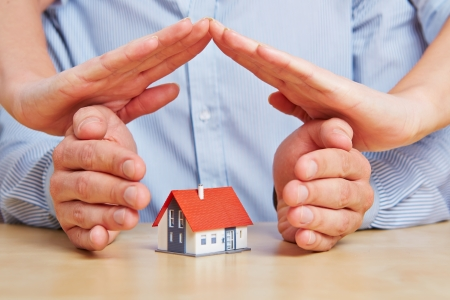 Four hands as a protecting roof over a little house Stock Photo - 16966009