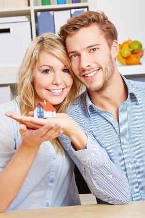 Smiling happy couple holding a little house on their hands photo
