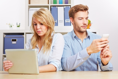 media room: Couple looking at tablet computer and smartphone seperately in living room