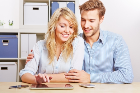 Couple playing around with a tablet PC and some smartphones in the living room Stock Photo - 16979725
