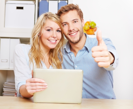 Happy couple holding thumbs up with smartphone and tablet PC in the living room photo
