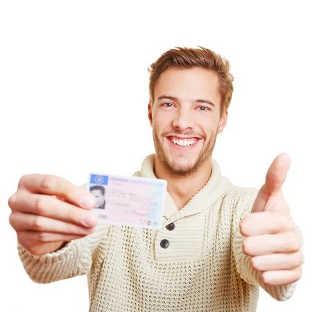 Happy man with his European drivers licence holding his thumbs up photo
