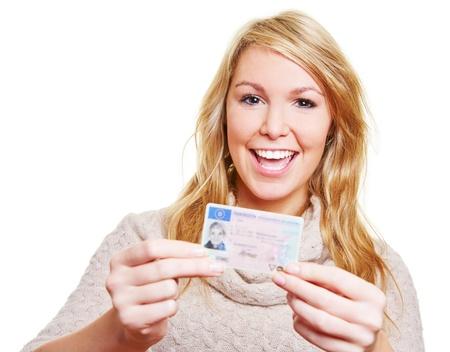 Glückliche junge Frau zeigt stolz ihren neuen Führerschein Standard-Bild