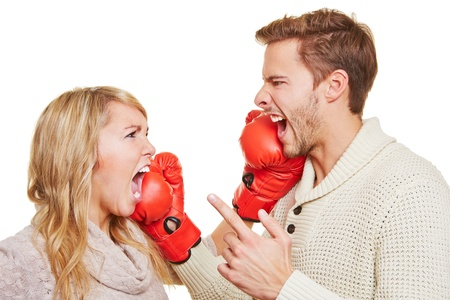 controversy: Screaming angry couple fighting with red boxing gloves Stock Photo