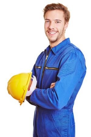 Happy smiling construction worker with yellow hardhat in blue overall photo
