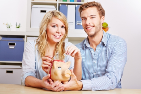 Young happy couple saving Euro money with a piggy bank photo