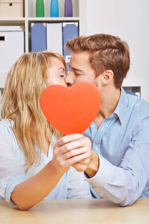 clandestine: Young couple kissing hiding behind a big red heart in the living room Stock Photo