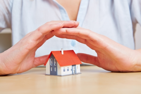 household insurance: Woman giving a small home safety with her hands as a roof