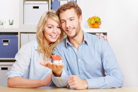 property insurance: Pareja sonriente que lleva una peque�a casa en las manos