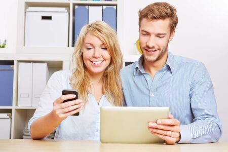 Couple synchronising a smartphone and tablet computer in the living room Stock Photo
