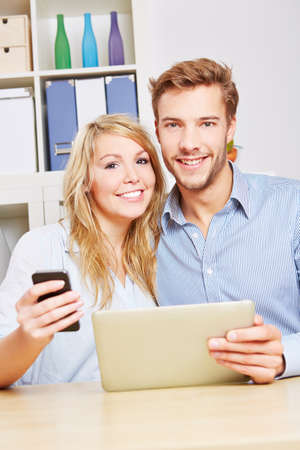Happy couple with smartphone and tablet computer sitting in the living room photo