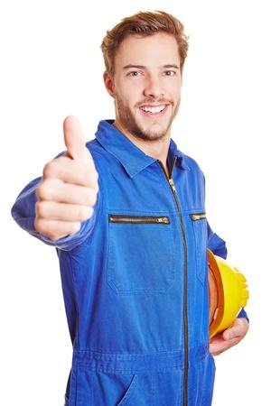 Gelukkig arbeider in blauwe overall met helm houdt zijn duimen omhoog Stockfoto