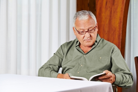 Senior man in rest home reading a book with reading glasses photo