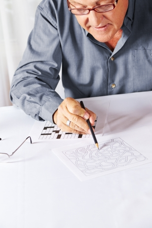 Senior with reading glasses solving a riddle in a rest home Stock Photo - 17660277