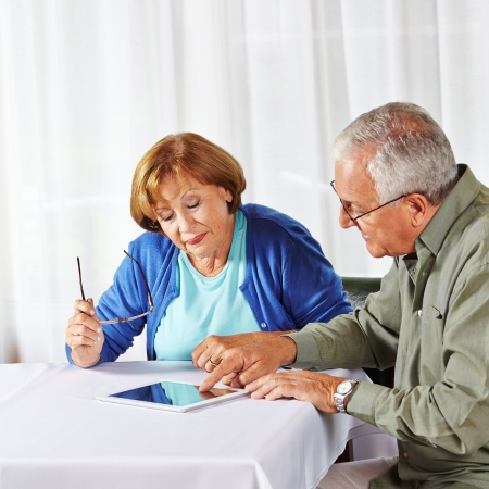 assisted living: Senior man showing old woman in nursing home a tablet computer Stock Photo