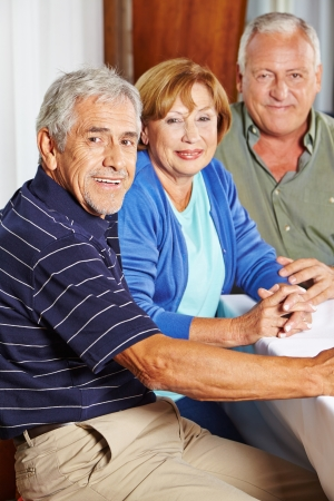 Portrait of three happy seniors sitting at table in a rest home Stock Photo - 17660214