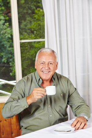 Happy retired man drinking a cup of coffee in a rest home Stock Photo - 17660298