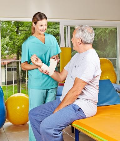 Smiling female hysiotherapist helping senior man in rehab photo
