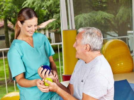 occupational therapy: Senior man doing exercises with spikey balls at physiotherapy Stock Photo