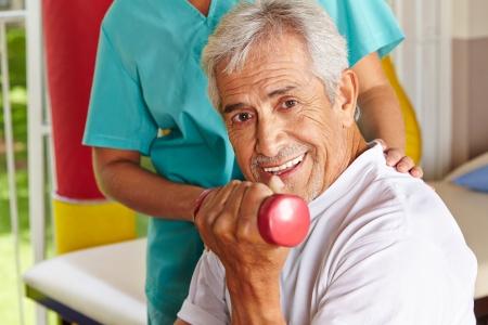 terapia ocupacional: Hombre mayor feliz que hace el entrenamiento con mancuernas en fisioterapia