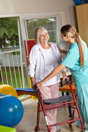 Physiotherapist explaining the use of a walker to a senior woman photo