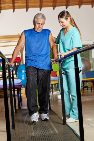 occupational therapy: Old senior man at physiotherapy holding on to handles Stock Photo