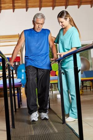 fysiotherapie: Oude senior man op fysiotherapie vast te houden aan handvatten