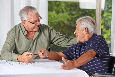 Two happy senior men solving crossword puzzle in a rest home photo
