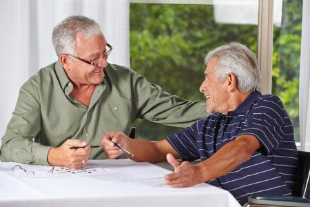 senior citizen: Two happy senior men solving crossword puzzle in a rest home