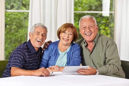 Three happy senior people with tablet computer in a retirement home
