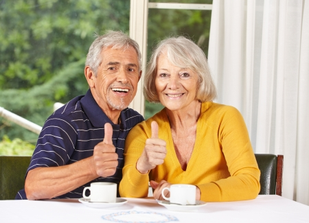 human thumb: Happy senior couple holding thumbs up at coffee table