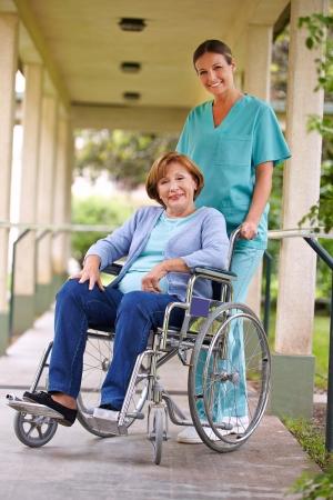 nursing treatment: Mujer mayor en silla de ruedas con una enfermera en el jard�n de una casa de reposo
